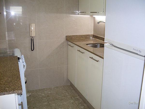 Imagen de la cocina, interior, decorada con modulares y estantes a tono, cerámicas y granitos de buen nivel.