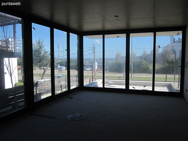 Vista general del living comedor del apartamento al lateral sur y frente a la Rambla Claudio Williman en planta baja.