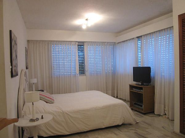 Vista general del dormitorio principal en suite. Las ventanas en la esquina miran hacia el frente – oeste – y al lateral sureste.