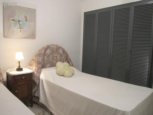 Uno de los dormitorios secundarios acondicionado con dos camas. Vista desde la esquina izquierda junto a la ventana hacia el placard.