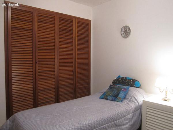 Uno de los dormitorios secundarios acondicionado con dos camas. Vista desde la esquina derecha junto a la ventana hacia el placard.