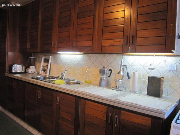 Detalle del acondicionamiento de la cocina con muebles bajo y sobremesada de gran capacidad confeccionados en madera.