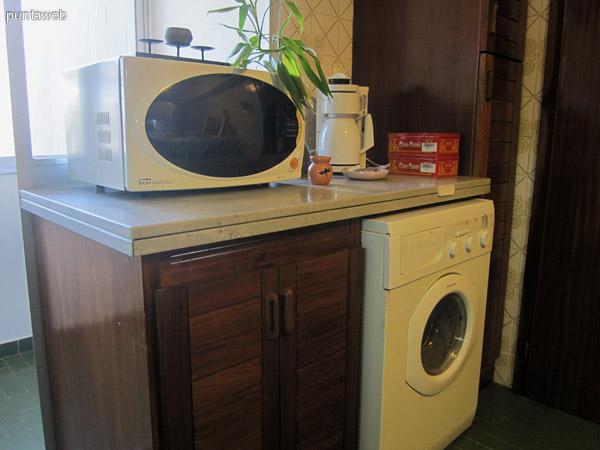 Detalle del espacio hacia el lateral sureste acondicionado con lavarropas, horno microondas y estantes bajo mesada.