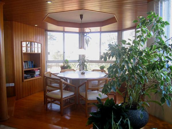 Estar a continuación del living comedor hacia la fachada sureste acondicionado con bow window y mesa para seis personas.
