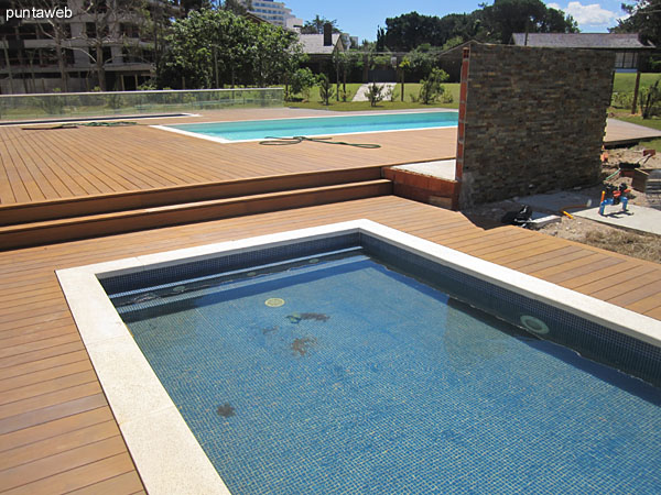 View of the pool for children in the large wooden deck of the property to the east.