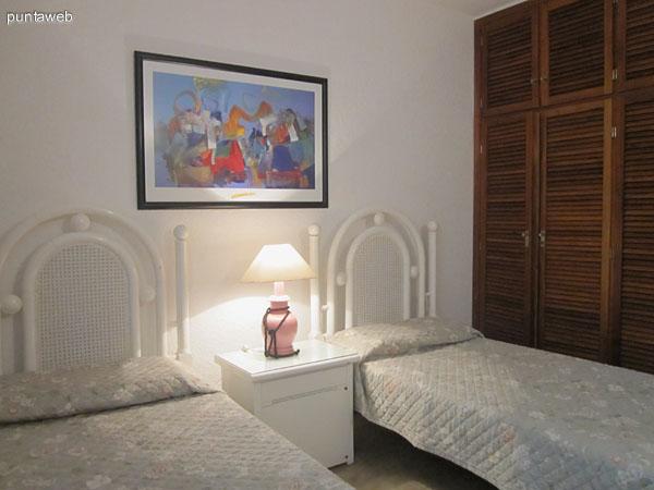 Dormitorio en suite al frente norte del departamento. Está acondicionado con dos camas individuales y placard en madera de buenas dimensiones.