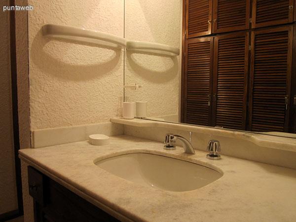 Vista desde la parte de servicios sanitarios y bañera hacia el espacio de placares y lavabo del baño en suite del dormitorio principal.