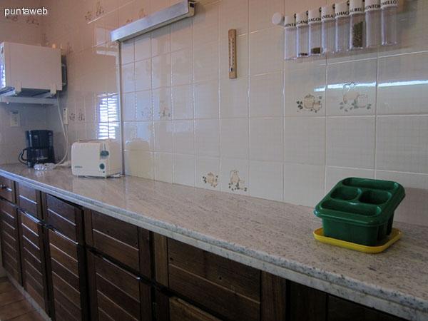 Mesada en la pared sur de la cocina. Acondicionada con muebles bajo y sobre mesada en madera y dos bachas.