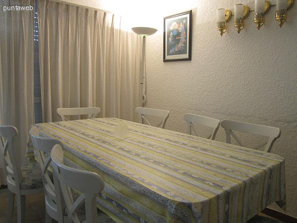 Mesa del comedor a la derecha del living. Está acondicionada con sillas para ocho personas.