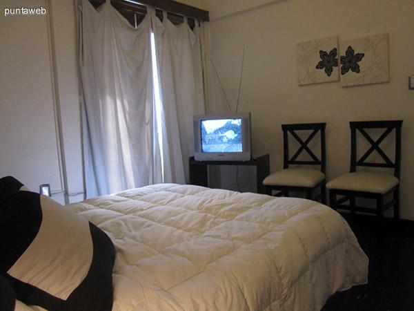 Dormitorio. Equipado con cama matrimonial y mesa con televisor. Brinda acceso por puerta–ventana al patio exclusivo con jard�n.
