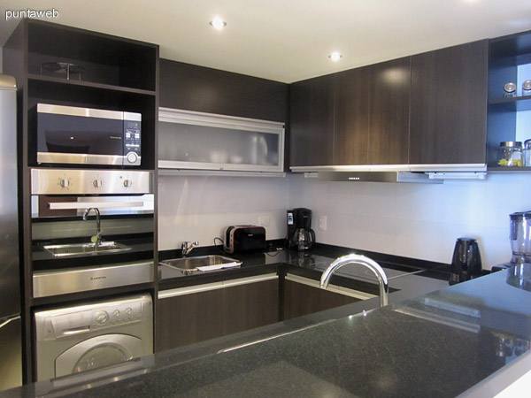 Cocina integrada. Barra de granito pulido. Modernos muebles bajo y sobre mesada de granito negro. Equipada con cocina vitrocerámica, horno microondas, horno independiente, lavavajillas, tostadora y cafetera.