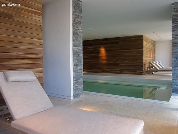 Reposeras en el espacio de la piscina climatizada. Los ventanales brindan vistas hacia el jardín posterior del edificio donde se encuentran las piscinas al aire libre y las barbacoas.