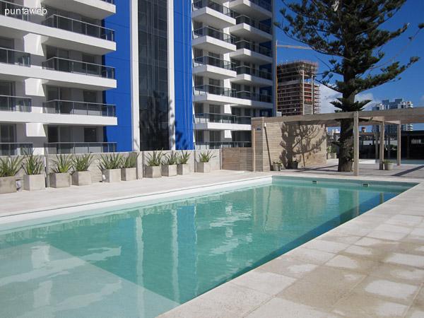 Vista general de la piscina climatizada. El espacio cuenta además con reposeras, sauna y duchas y brinda vistas por ventanales hacia el jardín trasero del edificio donde se encuentra las piscinas al aire libre y las barbacoas.