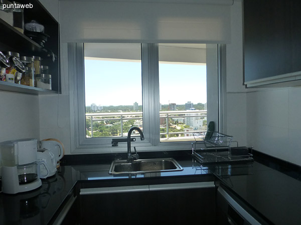 Detalle de armarios y estantes en la cocina. Existen amoblamiento bajo y sobre mesada en ambos laterales.