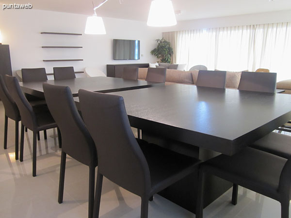 Defined space equipped with modern dining wood tables for 12 people.<br><br>To the right of the image, the kitchen visually connected  with the environment.