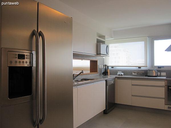 Lateral oeste de la cocina. Acondicionada con modernos muebles bajo mesada, campana extractora y ventanas exteriores.