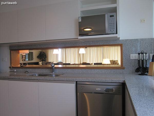 Detalle de mesada y cocina vitrocerámica.<br><br>Al fondo, muebles bajo y sobre mesada y la barra que conecta con el ambiente de comedor.