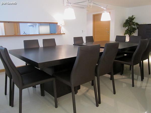 Espacio definido de comedor acondicionada con modernas mesas en madera para 12 personas.<br><br>A la derecha de la imagen, cocina conectada visualmente con el ambiente.
