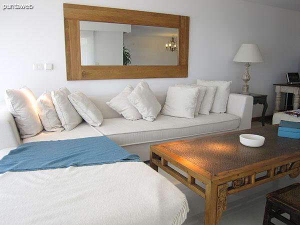 Detalle de ambiente de estar en el living. Situado al frente junto a la ventana sobre el lateral oeste, está acondicionado con mesa baja rectangular en madera y gran sillón en L de tres y dos cuerpos.