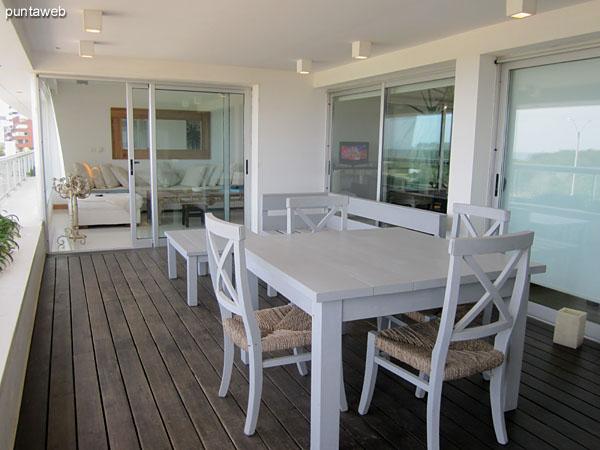 Balcón terraza techado del apartamento. <br><br>Equipado con parrillero y acondicionado con grupo de banco, mesa cuadrada baja y mesa cuadrada con cuatro sillas.<br><br>Este espacio se accede tanto desde el living como del comedor como del dormitorio principal.
