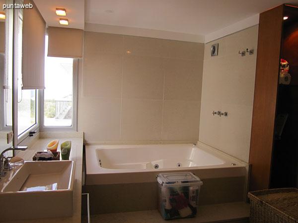 Baño en suite del dormitorio principal.<br><br>Desarrollado en un espacio que integra mesada con dos bachas rectangulares, gran espejo e hidromasaje con dos gabinetes cerrados con puertas de vidrio esmerilado donde se acondiciona la ducha y los artefactos sanitarios respectivamente.
