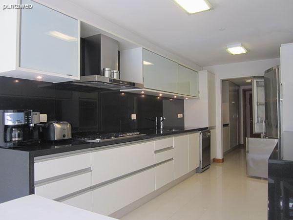 Detalle de la ventana con celosías en aluminio y puerta con acceso a la cocina del espacio del lavadero.