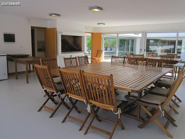 Espacio de barbacoa. Cuenta con una parrila, dos grandes mesas cuadradas en madera con 9 sillas plegables en madera cada una, además de freezer, heladera y horno microondas.