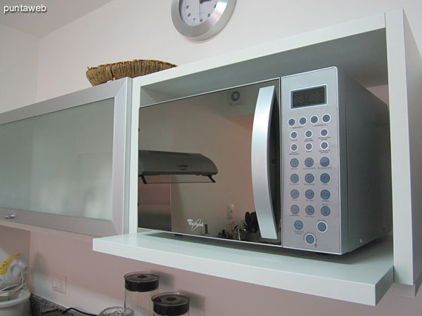 General view of the kitchen and into the field of refrigerator, microwave and shelves in height.