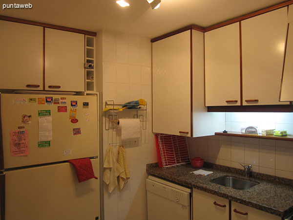 Partial view of the kitchen from the front door to the southeast corner.<br><br>Refrigerator.
