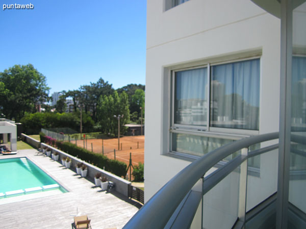 General view of the outdoor pool and solarium space from the apartment balcony.