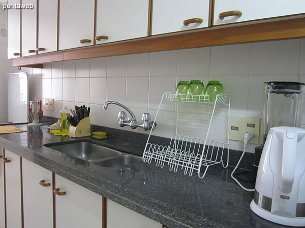 Detail of the shelves in the kitchen and table against the wall with two chairs and breakfast bar.<br><br>Provision of microwaves.