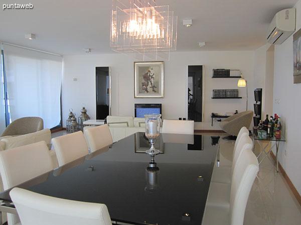 Detalle del espacio de comedor. Acondicionado con mesa en metal y vidrio con ocho sillas.