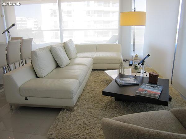 Detalle de sillón principal en el ambiente de estar frente al ventanal al ancho del apartamento con vista al mar.