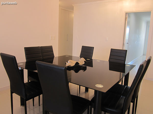 Balcony. It features barbecue. Detail game round table in glass and metal with four chairs.