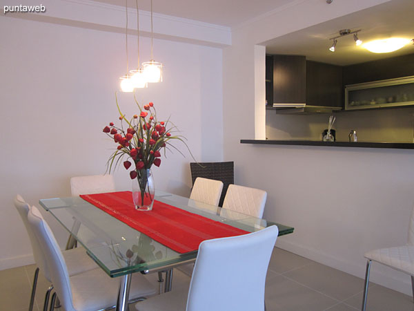 Access to the apartment. In the foreground the dining room and the background image kitchen with integrated bar.