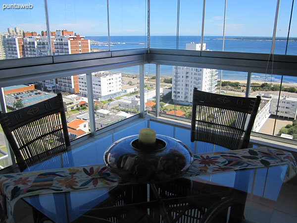 The balcony is closed in L and has barbecue and square glass table with four chairs.