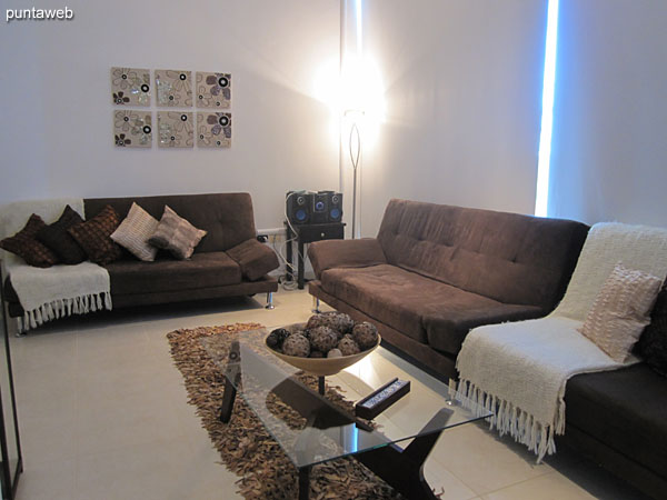 Living space on the second floor of the duplex. Equipped with three sofa around a rectangular glass low table.