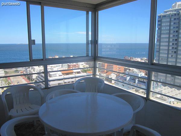 Detalle de la mesa con cuatro sillas de plástico en el balcón terraza cerrado del apartamento.