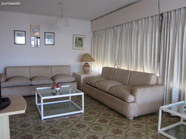 Vista general del ambiente de estar en el living comedor.<br><br>Acondicionado con dos sillones de tres cuerpos en torno a una mesa baja en madera y vidrio.<br><br>Cuenta con televisor con conexión a TV Cable.