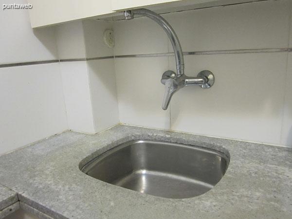 Detalle de la cocina a gas y eléctrica y mesada con estantes.