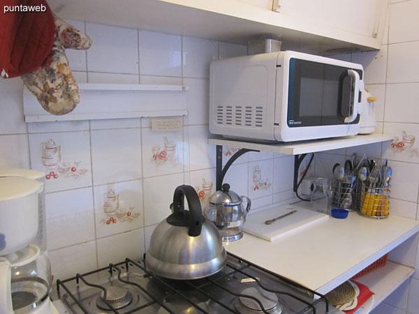 Cocina a gas de cuatro hornallas, horno microondas, heladera con freezer.