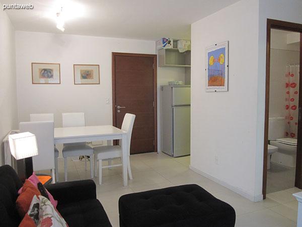 Espacio del comedor a la derecha del ingreso al apartamento. Equipado con mesa en madera y seis sillas.