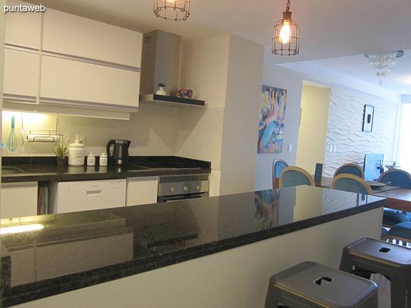 Vista general de la cocina, interior, tipo americana.<br><br>Equipada con mesada con doble bacha en acero inoxidable, muebles y estantes sobre y bajo mesada.