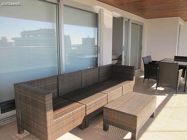 Vista general del balc�n terraza del apartamento. Accesible desde todos los ambientes del apartamento.<br><br>Equipado con mesa rectangular en vidrio y s�mil ratt�n con seis sillas, sill�n de tres cuerpos y otros elementos de estar.