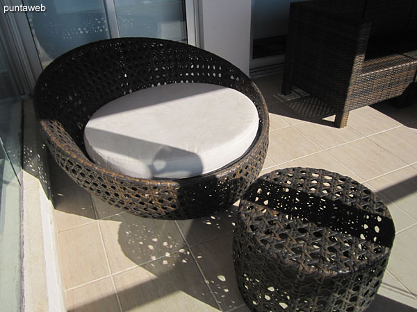 Detail of three bodies armchair in rattan simile in the apartment balcony terrace.