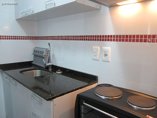 Kitchen, interior. Equipped with electric stove with two burners with electric oven, extractor, microwave oven and refrigerator with freezer.<br><br>It has an allowance of simple bacha in stainless steel, furniture under table and shelves on counter.