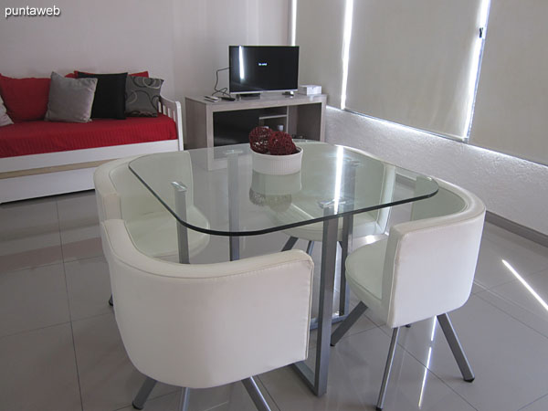 Square table detail with rounded corners in glass with four individual armchairs.