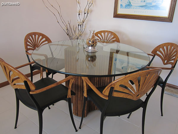 The dining room has a round glass table with four chairs.