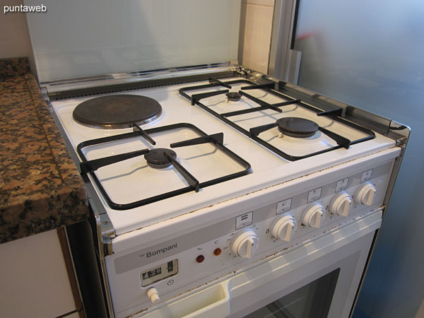 Kitchen with three gas burners and an electric burner.