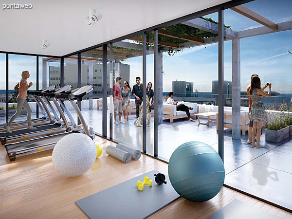 Espacio de gimnasio y terraza con solárium y barbacoa en la azotea.